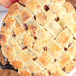 Pie with lattice crust and pie leaves in dual handle cast iron pie pan.