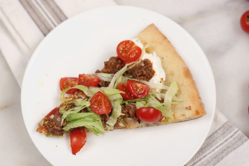 slice of taco pizza on a white glass plate