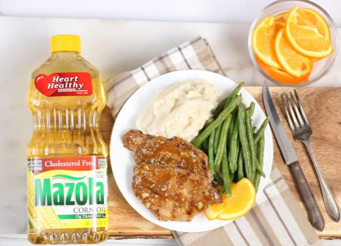 pork chops on white dish with fresh green beans and mashed potatoes, orange slices in clear glass bowl to right