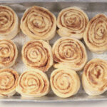 unbaked cinnamon rolls in a rectangle baking pan