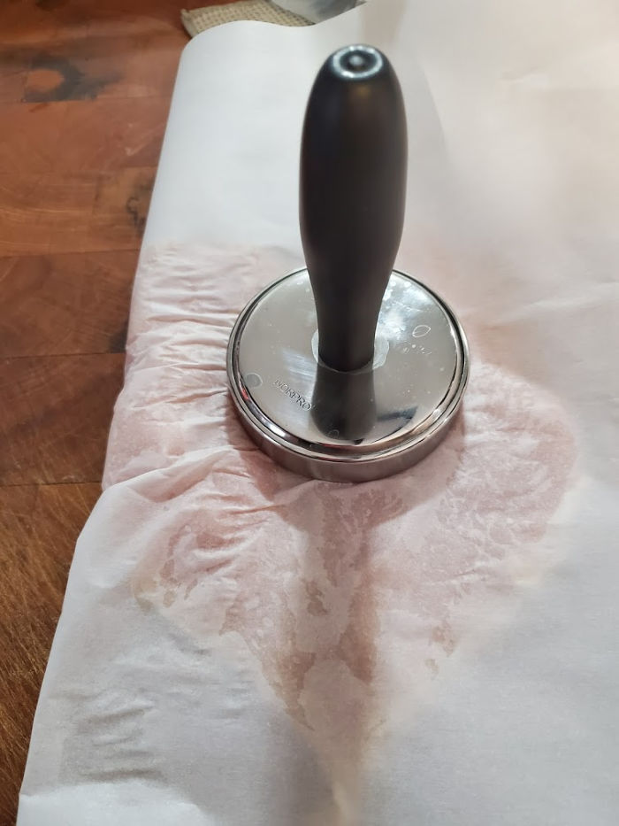 handled meat pounder flattening chicken in between butcher paper