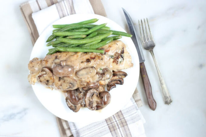 spinach stuffed chicken breast with mushrooms and cream sauce on white plate with fresh green beans