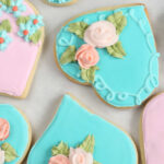 Heart shaped decorated sugar cookies with pink and teal icing and sugar flowers.