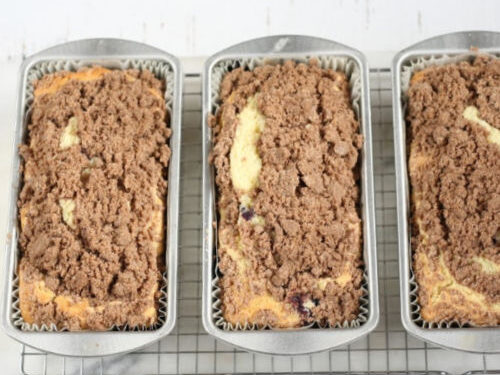 coffee cakes in metal loaf pans topped with streusel topping