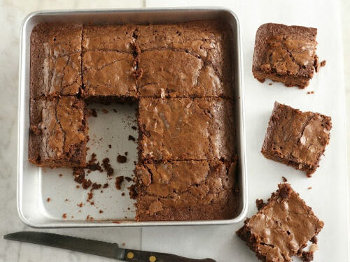 fudge brownies in a square metal baking pan, some cut up on side