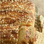 Oatmeal bread sliced on wooden cutting board