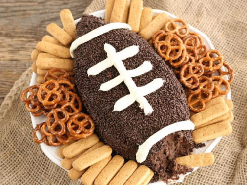 football shaped brownie batter dip with graham cracker sticks and small pretzels