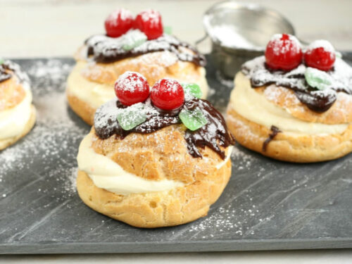 cream puffs topped with chocolate ganache, maraschino cherries, mint leaf candies, and dusted with powdered sugar