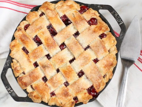 cherry pie with lattice crust in two-handle cast iron pan