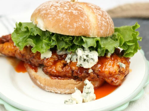 buffalo fried chicken on sandwich roll with chunks of blue cheese and green leaf lettuce