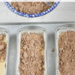metal loaf pans with coffee cake batter, cinnamon crumb topping on top and in blue speckled bowl in background