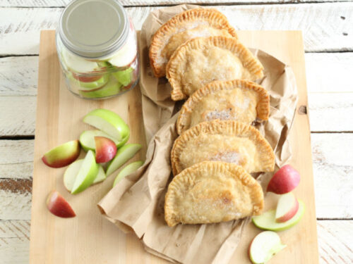 fried apple hand pies stacked up against each other on wooden cutting board, fresh slices of apples around