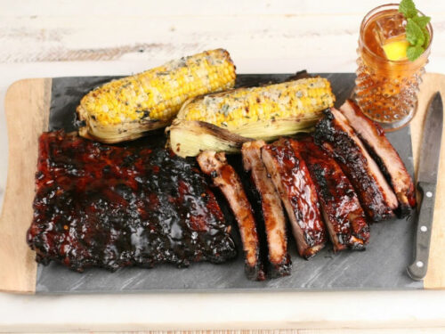 barbecue ribs cut up on wood and slate cutting board
