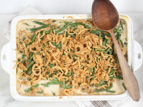 green bean casserole in white ceramic rectangle dish, handmade wooden spoon on right of dish