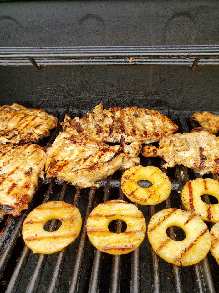 pineapple slices and grilled chicken on gas grill