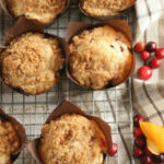 cranberry orange muffins on metal baking rack.