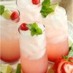 cocktail glasses with ice and strawberry drinks, on white footed cake dish