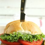Grilled chicken sandwich on round roll, topped with tomato slices and green leaf lettuce, steak knife through sandwich
