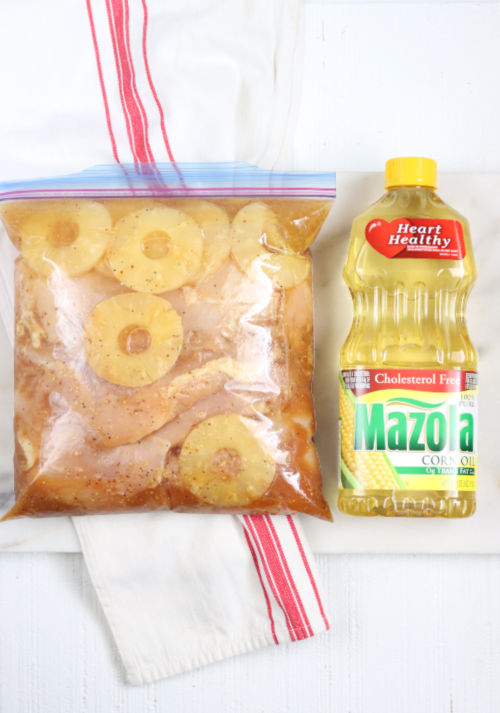 boneless skinless chicken in a large Ziploc bag with brown sugar pineapple marinade