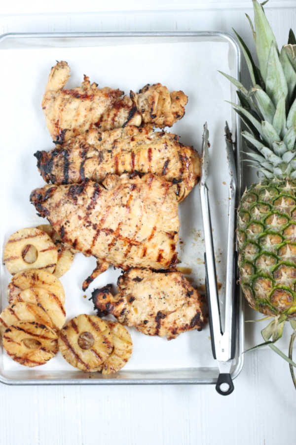 Grilled chicken on half sheet pan lined with parchment paper, whole pineapple to right