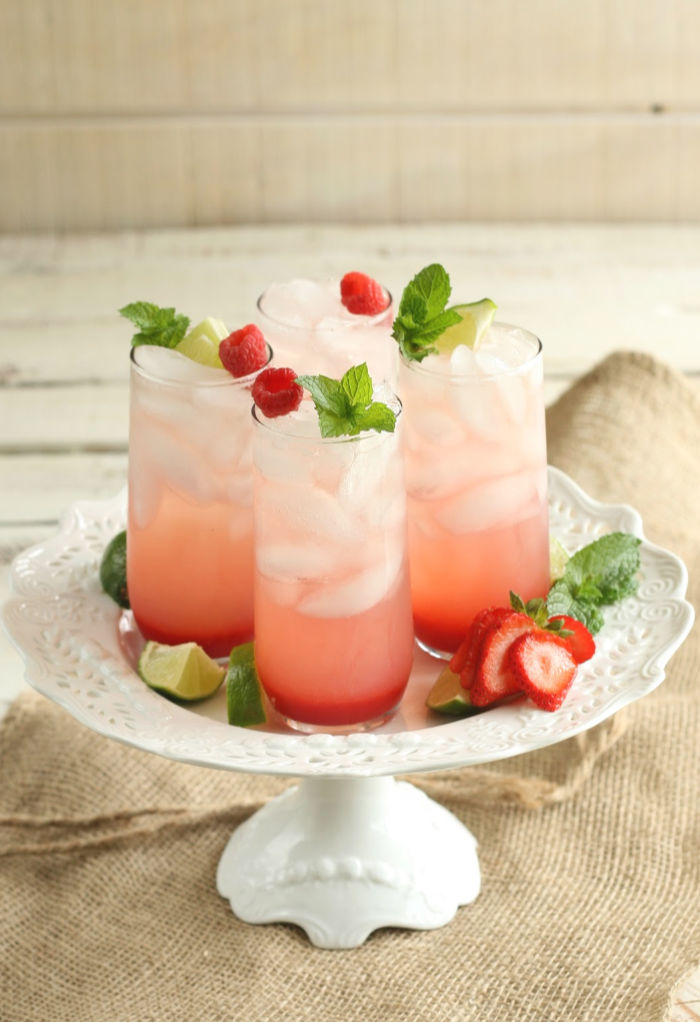 glasses of strawberry cocktails on a white footed cake dish, fresh strawberries sliced