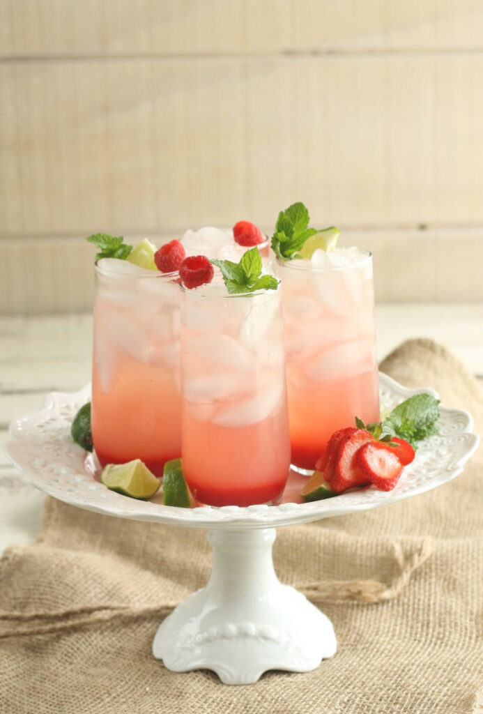 four glasses of strawberry cocktails on a white footed cake dish
