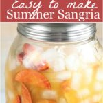 sangria with fresh peaches in a clear glass drink dispenser