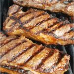 NY strip steaks on charcoal grill with grill marks, small flame below the grates