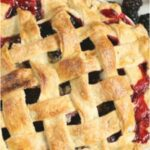 blackberry pie with lattice crust, juices overflowing on sides of pie
