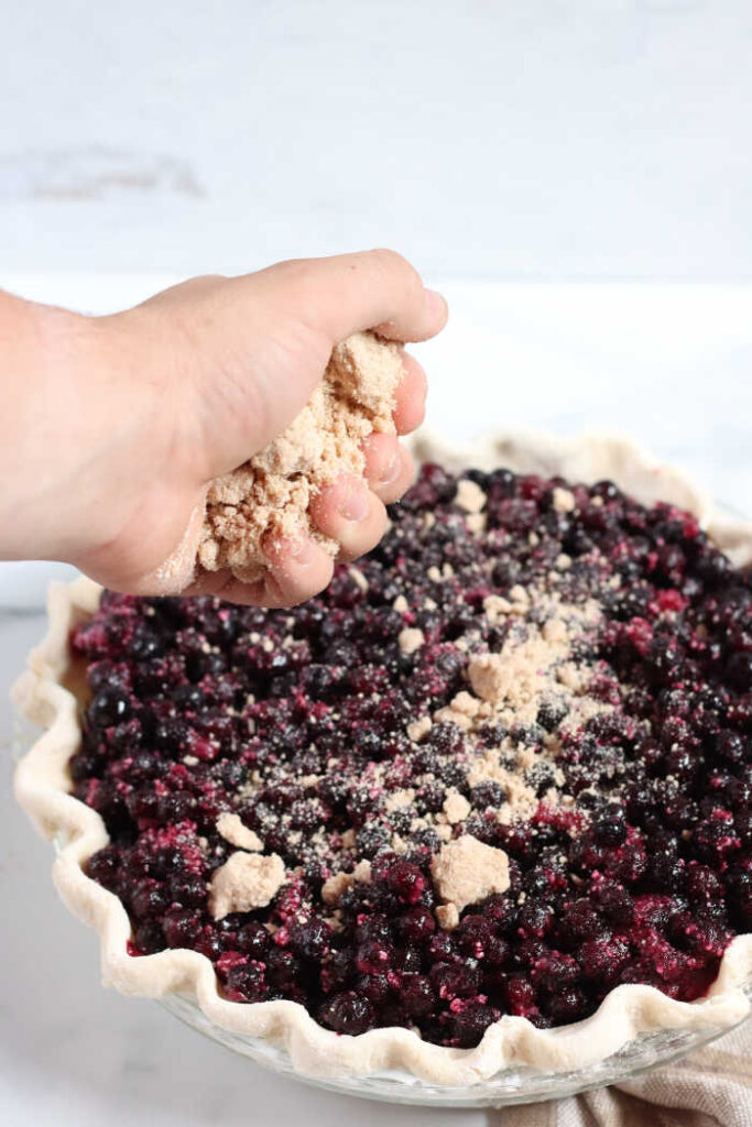 hand pouring crumble topping over unbaked blueberry pie