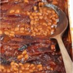 baked beans topped with crispy bacon in a white baking dish
