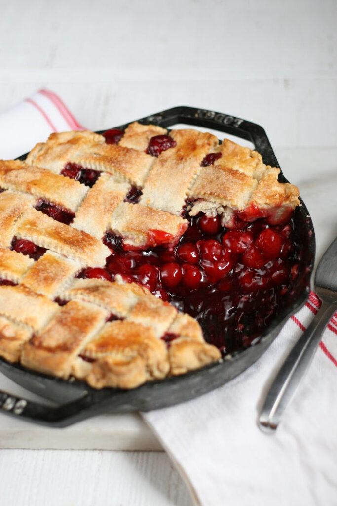 cherry pie in cast iron skillet with lattice crust.