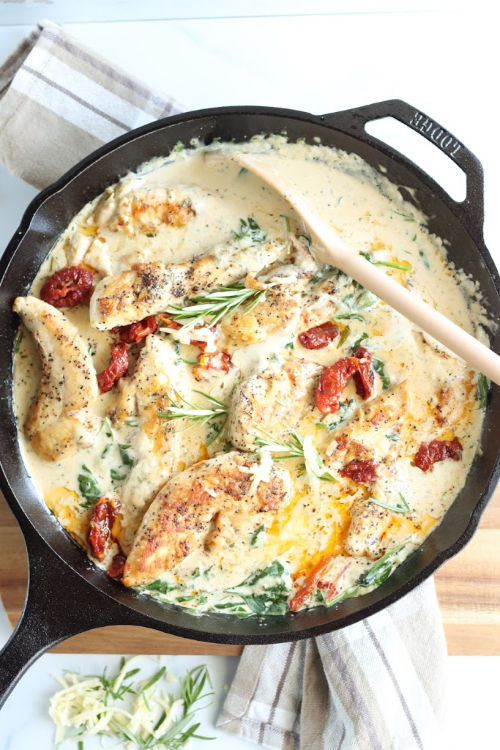 Chicken in cast iron skillet with sun dried tomatoes, spinach, and fresh rosemary