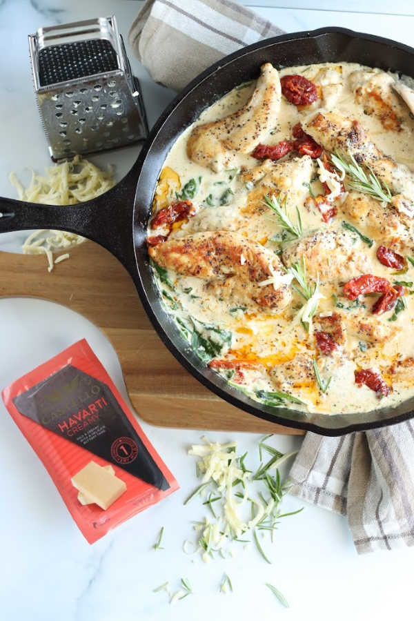 large cast iron pan with chicken cutlets, cream sauce, spinach, and sun dried tomatoes