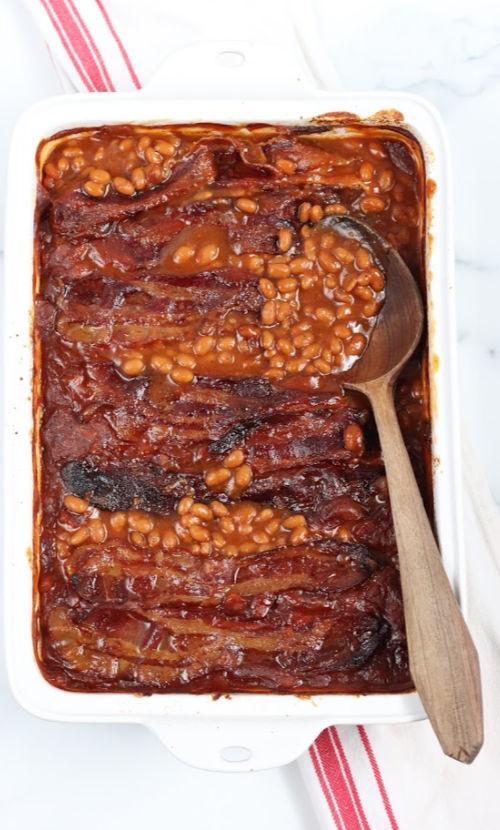 white ceramic baking dish with baked beans, topped with crispy bacon, wooden spoon in right side of dish