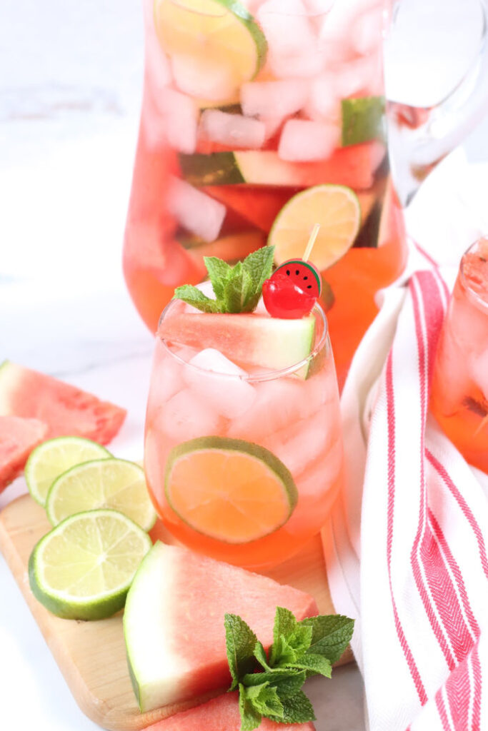stemless wine glass with pink sangria, lime slices, ice cubes, and watermelon slices surrounding glasses