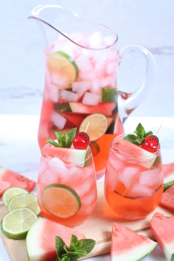 glass pouring pitcher with watermelon sangria, slices of watermelon on wooden cutting board surrounding