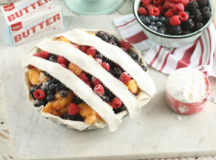 starting to weave a lattice crust on berry and peach pie. Red plastic measuring cup with flour on right, bowl of mixed berries near pie