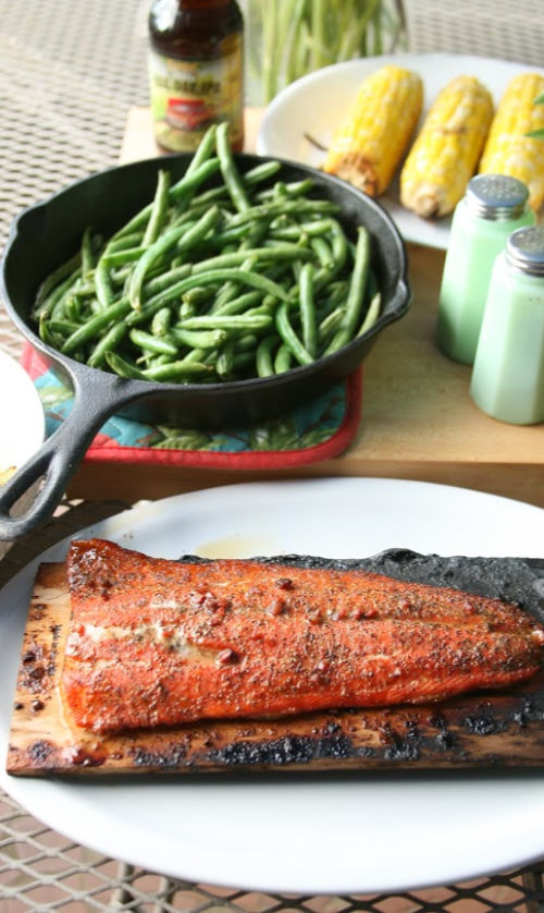 grilled salmon on a wooden plank on patio table with green beans in cast iron skillet, corn on the cob on white serving plate