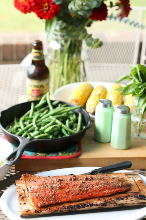 outdoor metal patio table with dinner of grilled corn on the cob, salmon on wood plank, green beans in cast iron skillet.