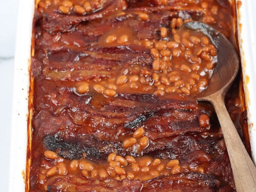 baked beans topped with crispy bacon in white rectangle baking dish, wooden spoon in right