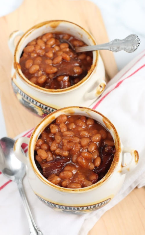small crocks with baked beans on wooden cutting board