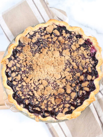baked blueberry pie with crumb topping, sitting on taupe plaid color kitchen towel on white marble