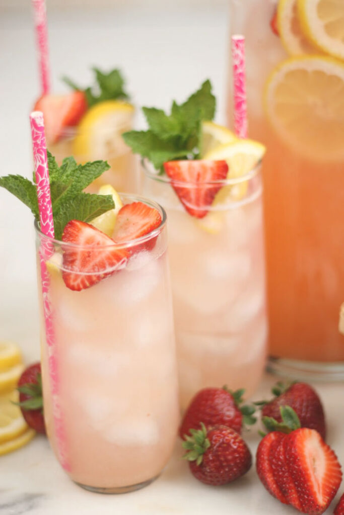 clear glasses of strawberry lemonade, lemon and strawberry slices, sprig of fresh mint, raspberry color paper straw