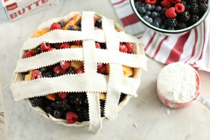 weaving a lattice crust on a mixed berry and peach pie. Cup of flour in red measuring cup to right, berries in bowl