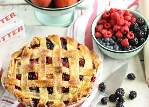 pie with lattice crust, berries in mint green metal bowl, fresh peaches in metal strainer