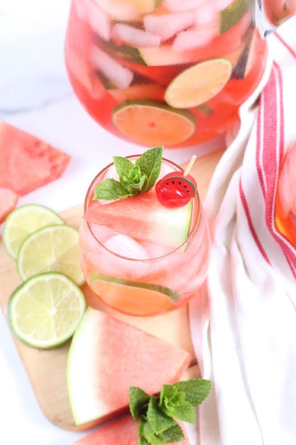 stemless wine glass with pink sangria, garnish of small watermelon slice and maraschino cherry