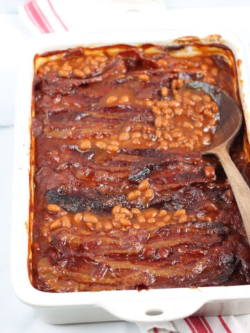 white rectangle baking dish with baked beans topped with crispy bacon, wooden spoon in right side of dish