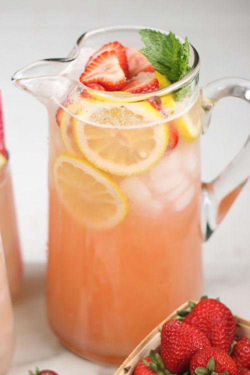 Clear glass pouring pitcher with strawberry lemonade, lemon slices, strawberry slices, and a sprig of fresh mint