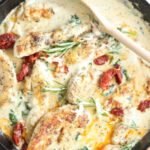 cast iron skillet with chicken tenders, cream sauce, sun-dried tomatoes, and spinach. Spoon to right of pan